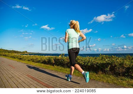 Middle-aged woman running at seaside