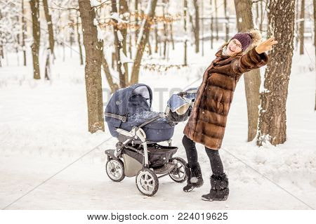 Young beautiful mother in a fur coat dancing while walking with a stroller in a city park at winter. Happy motherhood concept. Enjoying carefree maternity . Easy parenthood.