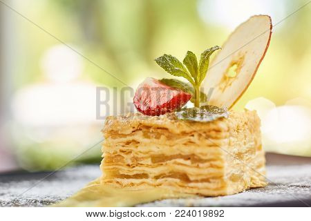 Side view close up napoleon cake with strawberry and apple. Napoleon cake layers and garnish close up.