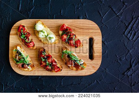 Italian bruschetta with tomatoes, Prosciutto di Parma, Mozzarella balls with pesto sauce, arugula and balsamic glasse sauce on cutting board. Mini sandwiches food set. Top view. Copy space.