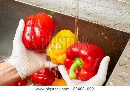 Water stream from tap falling onto bell peppers. Close up three wet bell peppers in hands.
