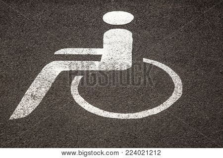 Handicapped parking space on asphalt - pictogram of a wheelchair user