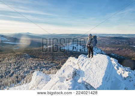 The mountaineer climbed the ice mountain top, man hiker standing at the peak of rock at sunrise