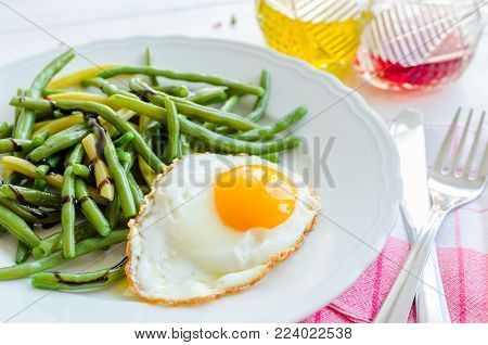 Cooked green beans with sauce balsamico glassa and fried egg in white plate on wooden background with red napkin, knife and fork. Healthy eating. Vegetarian food concept.