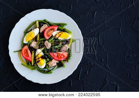 Summer warm salad with green beans, tuna, tomatoes, boiled eggs and sauce balsamico glassa in white plate on black stone background with place for text. Healthy eating concept. Top view. Copy space.