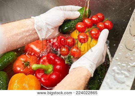 Washing vegetablea in a sink. Water flowing on vegetables in a sink.