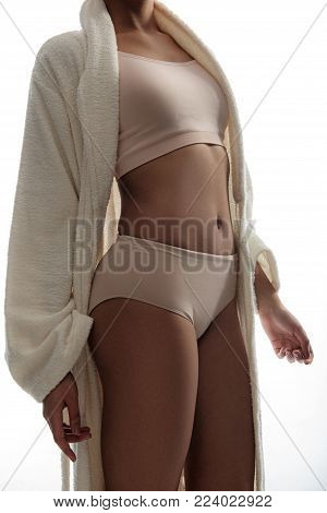 Slim female person posing in white bathrobe and classic underwear that flatters her shape. Isolated on background poster