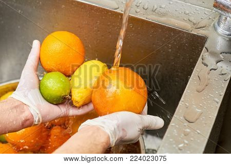 Citrus fruits assortment washing in a tap water. Tap water splashing on citrus fruits.