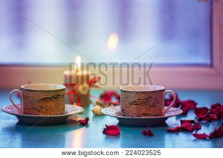 Valentine's Day, romantic dinner - two vintage cups of coffee are standing on a green surface with pink rose petals next to  burning candle with a heart symbol on window blurred background.