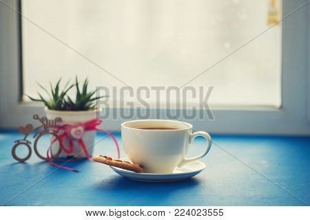 Valentine's Day, breakfast for your favorite - cup of coffee with a cookies stands on a blue surface, next to a cactus and a bicycle symbol with a heart on the window blurred background.