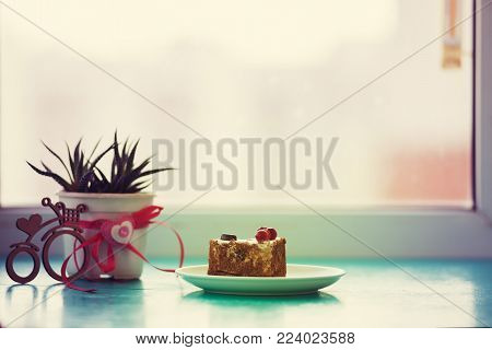 Valentine's Day, breakfast for your favorite - heart-shaped cake, stands on a green surface, next to a cactus and a bicycle symbol with a heart on window blurred background in light of sun.