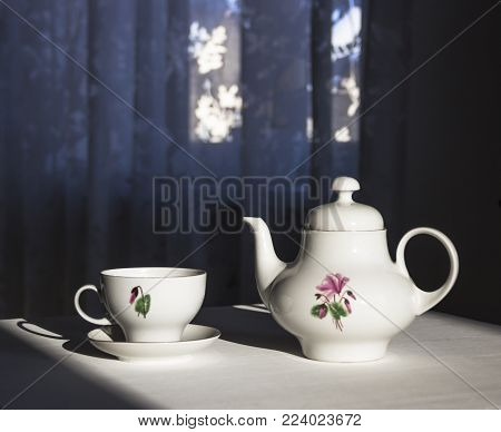 on the table a kettle and a cup in the sunbeam