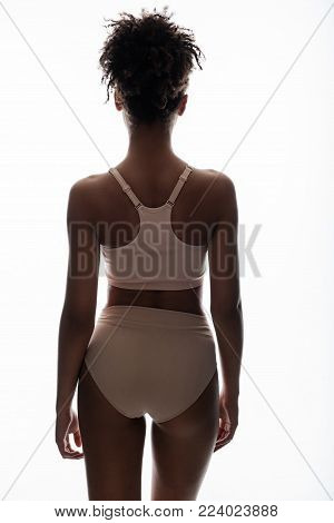 Calm woman with good forms standing with her back. She is posing in tight panties and brassiere. Isolated on background