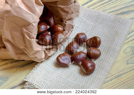 Sweet, useful, edible chestnuts (Castanea sativa) in a paper bag on a wooden table close-up