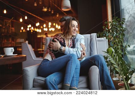 Man and woman drinking coffee in a cafe. Two people, man and woman in cafe communicate, laughing and enjoying the time spending with each other. Couple in love on a date. Love story and Valentines Day concept