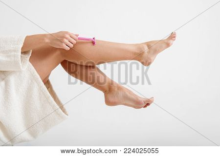 Close up of woman taking care of fit legs. She is using disposable razor. Isolated on background