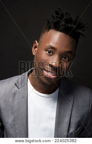 Close-up portrait of handsome black man with charming smile. Studio shot of well-dressed african guy wears white T-shirt and gray jacket, on dark background