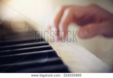 Blurred background with a synthesizer and the musician's hand.
