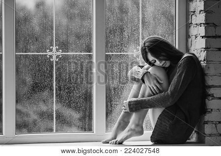 Beautiful young woman sitting alone near window with rain drops. Sexy and sad girl with long slim legs. Concept of loneliness. Black and white