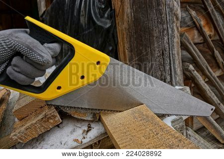 hand with a hacksaw cuts a wooden board