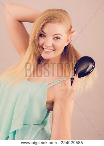 Hapyy joyful blonde woman brushing her beautiful long light blond hair seing results of haircare beauty treatment.