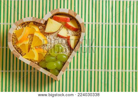 mixed fruits in heart shaped bowl. Healthy food concept.