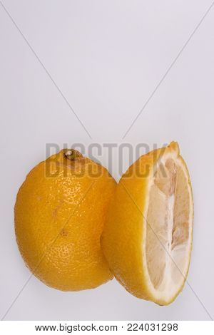 Lemon, cut into halves: half of the fruit stand side by side, skinned to each other, vertical frame, top empty space for text.