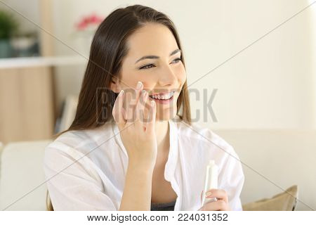 Portrait of a beauty woman applying moisturizer cream on the face sitting on a couch in the living room at home