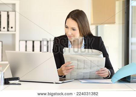 Executive comparing news online in a laptop and a newspaper at office