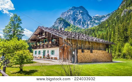 Panoramic view of idyllic mountain scenery in the Alps with traditional farmhouse and fresh green mountain pastures with blooming flowers on a sunny day with blue sky and clouds in summer