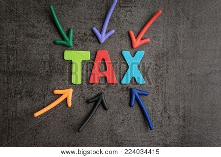 Important of tax in accounting business, colorful arrows pointing to the word TAX at the center on black cement wall, financial income have to pay or refund yearly government tax by law.
