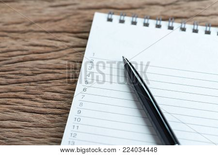 Personal to do lists or work, tasks priority concept, closed up of list of numbers on white clean paper notepad with black pen on wood table in soft tone, organize or writing projects.