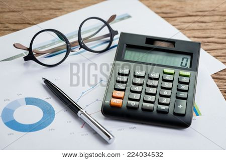 Accounting equipments, work corporate profit or finance calculations, savings concept with pen, calculator and eyeglasses on graph and pile chart paper, KPI or client campaign analysis.