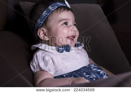 Close-up portrait of a laughing little baby girl on sofa. 5 months old baby, side view.