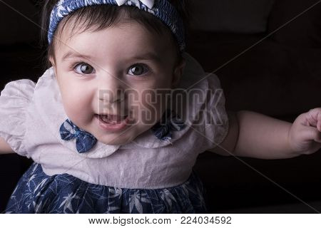 Close-up portrait of a happy 5 months old little baby girl on sofa. Wearing blue and white cloth.