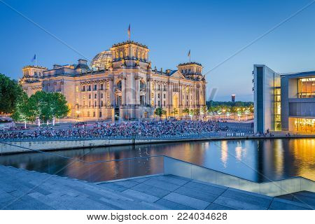 Panoramic view of modern Berlin government district with famous Reichstag building and Spree river illuminated in beautiful post sunset twilight during blue hour at dusk, central Berlin Mitte, Germany