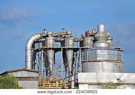 Steel factory separating chimney over blue sky