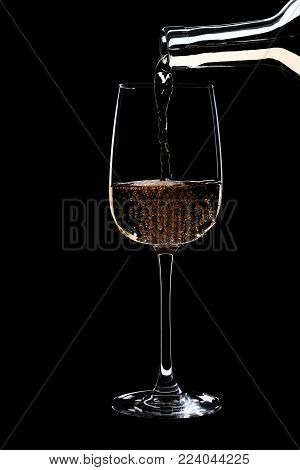 A glass of white wine is pouring wine from bottle of white. Filmed in close-up glass, where you pour the wine from the bottle.