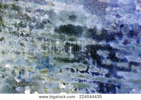 Close up photograph of a handmade metallic abstract background texture. Shades of blue and green are speckled with flecks of silver.
