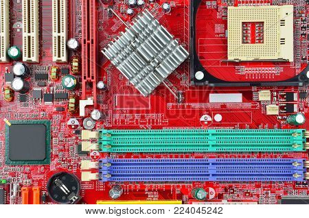 Red printed computer motherboard with microcircuit, close-up