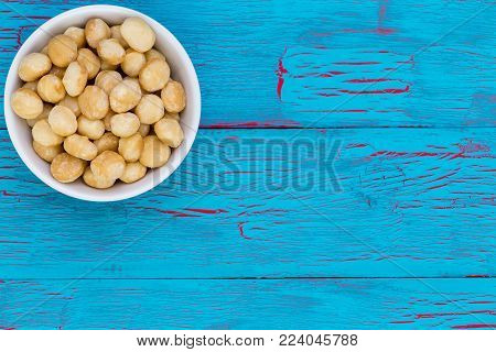 Generic white bowl filled with fresh whole shelled macadamia nuts rich in nutrients over a blue crackle painted wooden background with copy space