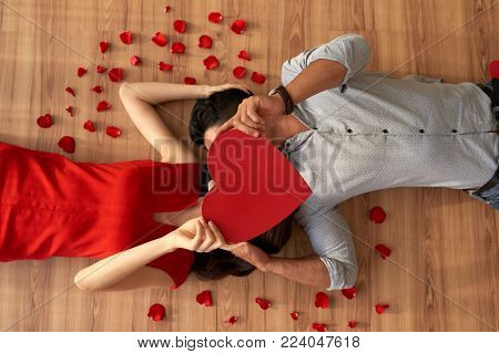 Directly above view of loving young couple covering their faces with heart shaped piece of paper and kissing while lying on floor, red rose petals scattered everywhere