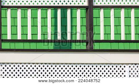 Architectural detail showing closeup of a traditional wooden painted house on Iles de la Madeleine, Canada. Green shingles with white wooden railing and trelis work.