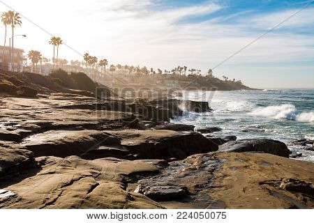 Eroded rock formations and cliffs on a hazy morning at Windansea Beach in La Jolla, California.