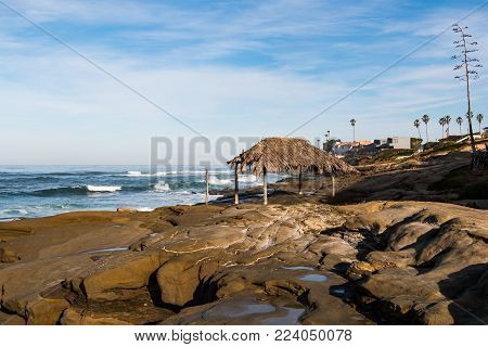 The thatched surfer shack built on rock formations at Windansea Beach in La Jolla, California.