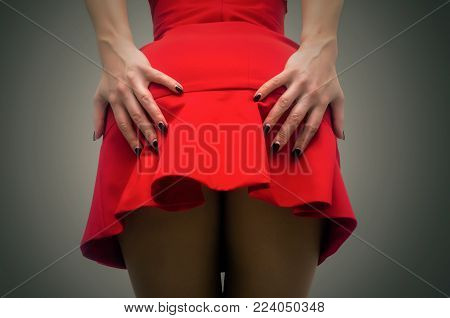 Sexy female hips in stockings behind and hand that holds a short red dress.