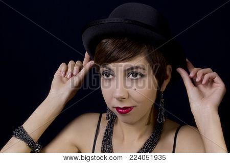 Portrait of a young woman in retro style in a bowler hat