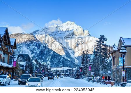 BANFF, CANADA - DEC 22, 2017: Winter scene on Banff Avenue in the Banff National Park with Cascade Mountain in the background. The townsite is a major Canadian tourist destination renowned for its mountainous surroundings and hot springs.