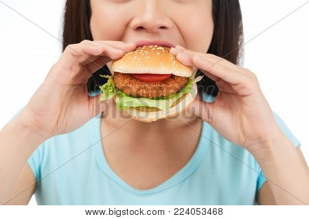 Close-up shot of young woman wearing blue T-shirt eating appetizing hamburger while standing against white background