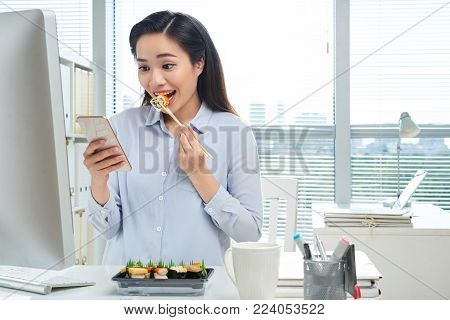 Cheerful Asian white collar worker texting with friend on smartphone while enjoying delicious sushi at workplace, panoramic window on background